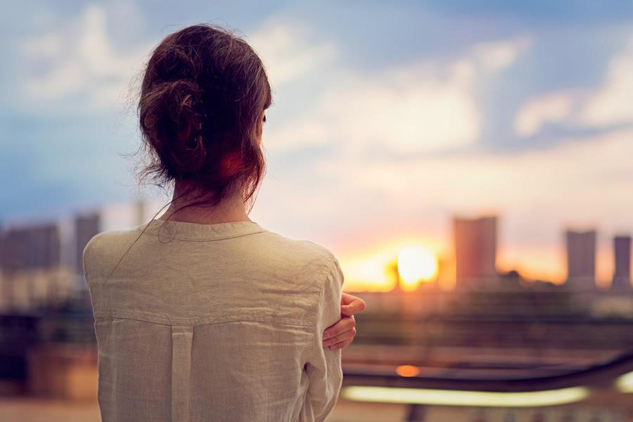 Jeune femme regardant un couché de soleil